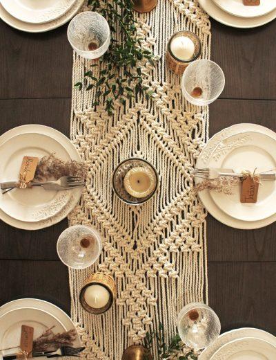 Padekoruotas stalas su žvakidėmis ir stalo takeliu šventiniam stalui