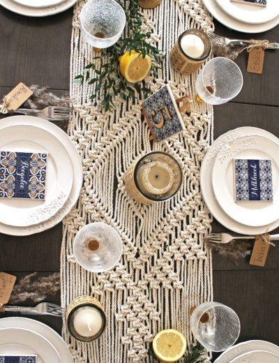 Stalas padekoruotas su žvakėmis, gėrimų padėkliukais, macrame stalo takeliu ir žalumynais