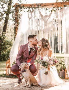 Jaunavedžių pora bučiuojasi priešais medinę arką ir foto sienelę