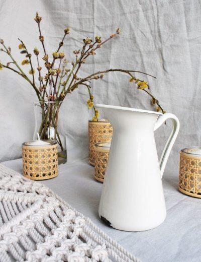Baltas metalinis ąsotėlis - vaza žvakidžių ir žydinčių šakelių fone